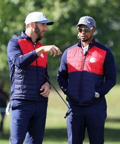 Dustin Johnson and vice-captain Tiger Woods of the United States speak during practice prior to the 2016 Ryder Cup at Hazeltine National Golf Club on September 27, 2016 in Chaska, Minnesota.