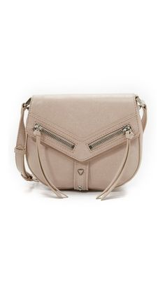 A saddle-shaped Botkier shoulder bag in glazed leather with polished studs. Long pulls hang from the magnetic front flap, and a slim pocket outfits the back. Wraparound zip at the gusset. Lined, interior. Womens Designer Bags, Small Bags, Handbag Accessories, Saddle Bags, Purses And Bags, Dust Bag, Shoulder Strap, Studs, Handbags