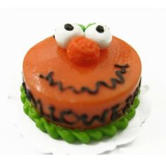 Happy Halloween Cake. www.teeliesfairygarden.com . . . Fairy Halloween Parties are not complete without a delicious main cake. This Halloween cake features a smiling pumpkin with chocolate and green icing. #fairycake