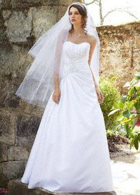 Elegant and unforgettable, you are a star in this lavish a-line wedding dress. Intricate beaded embroidery on bodice is stylish and creates a stunning slimming focal point. Luxurious satin fabric is durable and will hold up beautifully throughout your special day. This side-draped beauty features beaded lace appliques. Chapel train. Sizes 0-14. Available in White online or by special order. Available in Ivory by special order only. Woman: Style 9WG3464, $649. Sizes 16W-26W. Back Zip. Dry…