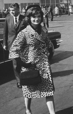 Saying goodbye to her husband John F Kennedy as she departs for a solo tour of India and Pakistan, wearing a stunning leopard coat, long black gloves and black pillbox hat. (1962)