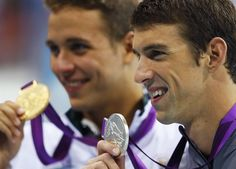 Michael Phelps holds his silver medal next to gold medal winner Chad le Clos of South Africa in the men's 200m butterfly victory ceremony.