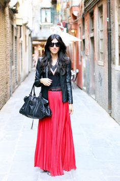 sweeping floor-length red pleated maxi skirt with black ribbon waistband by enza costa   paired with a peaked shoulder structured leather blazer jacket, black tank and black balenciaga large city bag   black oversized square tom ford sunglasses   venice italy