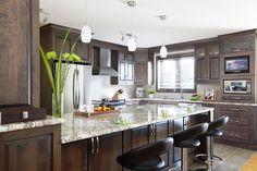 îlot et armoires de cuisine classique ont été réalisés en placage de merisier teint.Comptoir en granit noir et poignées horizontales en acier.
