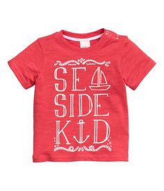 En t-shirt i bomullstrikå med tryck. Tryckknappar på ena axeln.