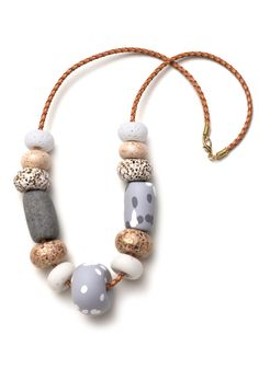 This necklace features a variety of sparkly, patterned and spotty hand-formed polymer clay beads threaded onto tan braided leather cord. It is avai...