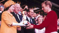 """Queen Elizabeth II presents the World Cup, the Jules Rimet trophy, to England""""s team captain Bobby Moore on 30 July, 1966"""