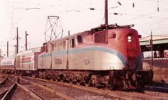 https://flic.kr/p/cPSL6f | Amtrak 924 on an Army-Navy Game special | A forty-year-old GG1 in the livery applied to all too few of the old PRR electrics heads a train of new Amfleet coaches in November 1975 arriving at Stadium in South Philadelphia with an Army-Navy Game train from Washington. The old GG1s were not converted for the newer head end power (HEP) and you can see a generator car between the engine and the train.