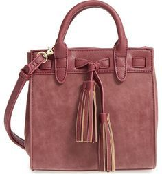 Dual tassels add a flash of vintage charm to this chic and compact everyday satchel.