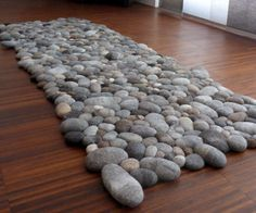 Give your bedroom some added texture that'll tie the room together by laying out this felt stones rug. This handmade rug is composed of dozens of differently sized felt pebbles each containing a soft foam core that make them ideal for stepping over or laying on.