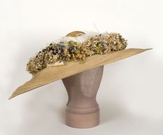 Wide-Brim Straw Hat Made From Natural Colored Straw, Decorated With Ivory Ostrich Plumes And Charming Bouquets Of Forget-Me-Not Like Fabric Flowers   c.1910