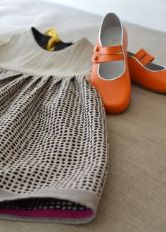 This double strap orange shoe is perfect with the black dots on the skirt of this dress.