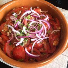 Gemarineerde tomatensalade. Tomaten gemarineerd in een heerlijke dressing en dan geserveerd met fijngesneden rode uienringen