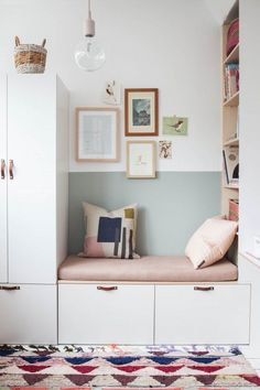 white  storage bench with leather pulls and a pink cushion with a half painted mint green wall