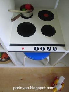 Materials: Ikea Expedit shelving unit, black contact paper, red and white electrical tapeDescription: I was planning to buy a white Brio stove for my daughter b