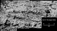 Калтех: жизнь на Марсе? This black-and-white mosaic of microscopic images shows fine, undulating, horizontal layers of rock-hard sediment stacked atop each other and interspersed with bead-shaped concretions of rock. Some of the layers curve upward in the shape of a smile. Here and there, an overlying layer cuts into previously deposited layers, creating a truncation in the underlying layers that curves upward at its lateral edges. These undulating, down-cutting layers are known as…