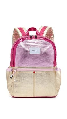 For every STATE bag purchased, STATE hand-delivers a backpack—packed with essential tools for success—to an American child in need..  A roomy STATE backpack with a mix of metallic colorblock panels. Zip front pocket and Velcro® side pockets. Wraparound top zip and lined interior with 7 pockets and 4 pen slots. Padded back. Locker loop and adjustable shoulder straps.