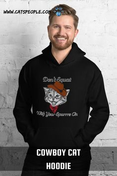 """""""Don't squat with your spurrs on!"""" a famous cowboy saying with a can pun! this cowboy cat design is purrfect for cat owners and cat lovers who are cowboy fans! A unique and cute design that will draw a smile on every cat mom and cat dad's face. Everyone needs a cozy go-to hoodie to curl up in, so go for one that's soft, smooth, and stylish. It's the perfect choice for cooler evenings! #catloverhoodie #catmomhoodie #catdadhoodie #catladyhoodie #cowboyhoodie #catcowboy #funnycathoodie #catpun"""