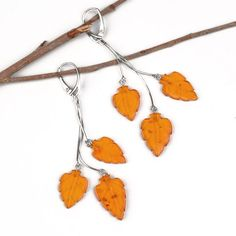 """Honey Amber Leaves Earrings Item No. AM03221A01 $30.79 Combining the perfect blend of sparkling sterling silver and soft color of honey amber leaves, these stunning earrings go perfectly with all types of outfits and looks. These eye-catching earrings dangle from polished sterling silver leverback clasps. Earrings' length is about 3 1/4"", each leaf is about 7/8"" long. There are three honey colored, hand carved amber leaves hanging from three silver chains."""