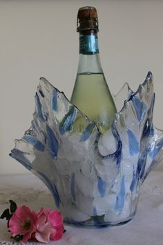 This art vase/ice bucket was created with greens and aqua blue to look like leafy vines on an icy background. The design is called Enchanted Leaves because it has a fairy tale feel to it. Each piece is hand cut and layered on a large piece of clear glass. It is fused and then literally draped by melting the glass over a form to achieve the organic folds.  This would be absolutely stunning on the bridal table with a bottle of champagne chilling, or at your next New Years Eve celebration…