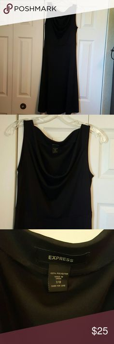Express Black Dress 7/8 Amazingly useful little black dress. Modestly comes down to the knee with a flowing skirt you'll love to move in. Clinches around the waist and flares out subtly. 100% polyester but is a nice heavy fabric that won't blow up in the wind. Drape neck is very flattering without exposing too much. Express Dresses Midi