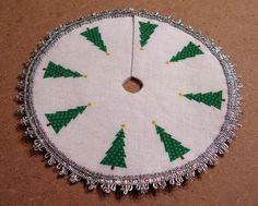 "I used Word to create a circle 4.5"" in diameter and then added clipart trees around the edge.  I printed it on fabric and adhered it to sticky-backed felt.  I then sewed some silver trim around the edge.  ottereine"