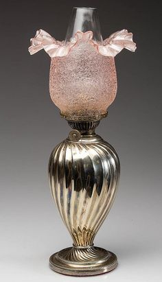 """SILVER-PLATED RIBBED SWIRL MINIATURE LAMP, with weighted circular foot, pale pink crackle overshot glass ruffled-top shade. Period burner with thumbwheel marked """"HINKS & SON BIRM"""", shade ring and chimney."""