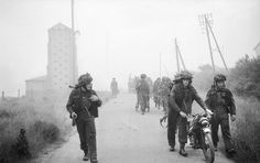 Commandos of 48 (RM) Commando, 4th Special Service Brigade, making their way inland with their equipment including a motorcycle and handcarts at St Aubin-sur-Mer, JUNO area,
