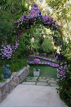 Colin Cowie Purple roses, arranged on a verdant garden archway, highlight a path to the lovely ceremony space.
