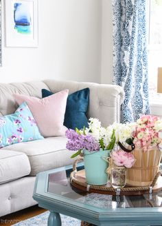 Beautiful pastels and florals showcased in this spring living room from The Happy Housie. #springdecor #springstyle #livingroom #thehappyhousie