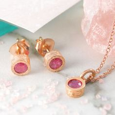 A stunningly simple and elegant 18K rose gold plated jewellery set featuring a single precious ruby stone in a naturally textured gold setting. #Embersjewellery #Jewellery #July #Birthstone #Ruby