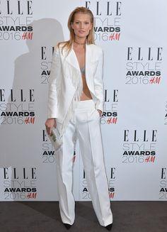 Modelo Tony Garn com calça de alfaiataria branca, blazer com franjas branco e sutiã de renda cinza.
