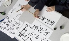 How to teach Chinese. Pupils learning Chinese caligraphy. Many schools are now teaching Chinese.
