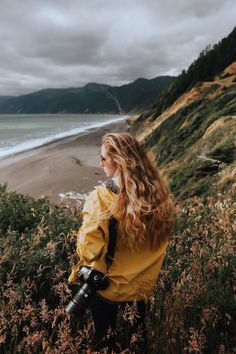 The Ultimate Travel Photography Gear List. Everything you need to know about how to be a travel blogger and photographer. Black Sand Beach California. Wearing yellow rain jacket, heather gray beanie and canon 5D mark III in a field of wildflowers on the cliffs by the Pacific Ocean