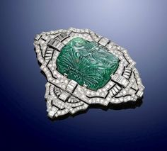 Art Deco white gold, diamond and carved emerald brooch, circa 1925