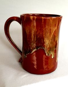 By Linda Neubauer  Firebrick x 2, a stripe of black glaze in center of mug, Albany Slip Brown x 2 top half of mug down to cover the stripe of black