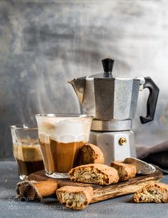 Pic: Glass of latte coffee on rustic wooden board, cantucci biscuits and steel…