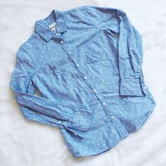 """J. Crew Chambray Boy Shirt in Dots Cute and classic chambray shirt from J. Crew. Retail, not from the factory store. Size 00. Great condition, just needs an iron on the fabric by the buttons to flatten it back out. ----------- Our favorite borrowed-from-him silhouette in a fresh dot pattern (we love that it's simple enough to function as a neutral, making print mixing a cinch). We added carefully placed seams at the bust for a subtly feminine fit. Cotton. Body length: 27"""". Long sleeves…"""