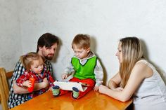 Mother, father, daughter and son involved in education using a Tablet PC sitting at the kitchen table. Family Stock Photo, Young Family, Sons, Father, Childhood, Stock Photos, Marketing, Education, Creative