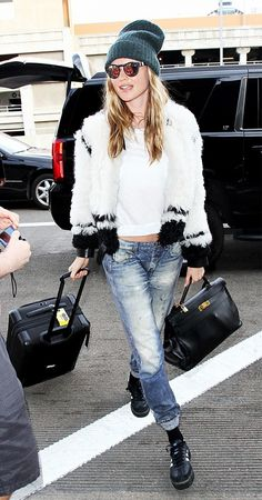 Behati Prinsloo wears a beanie, fur coat, white crewneck, baggy jeans, a black top handle bag, and black boots