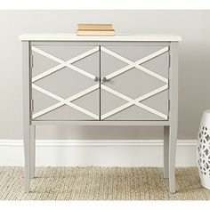 The crisscross design of the gray-finished Safavieh Winona Sideboard makes it a timeless classic fit for any home. Store away items in the ample storage space hidden behind two cabinet doors or display decorations on the top shelf for visitors to behold. Use this versatile piece in a hallway or perhaps in the kitchen with