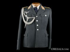 This excellent Flight Section Luftwaffe Colonel uniform has the four pockets with flaps and all buttons are the aluminum pebbled type. Carefully hand sewn, is a beautiful officers droop tail Luftwaffe breast insignia. The collar is piped with aluminum bullion and the collar tabs are beautiful yellow color velvet background with a full bullion wreath. The wreath is highlighted with crisp acorns. Inside the wreath are three birds, indicating the colonel rank. Ww2 Uniforms, Three Birds, Luftwaffe, Hand Sewn, World War, Wwii, Crisp, Breast, Suit Jacket