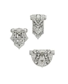 A GROUP OF THREE ART DECO DIAMOND CLIP BROOCHES Of geometrical openwork design, set with circular and baguette-cut diamonds, two of them also with triangular-shaped diamonds, circa 1925