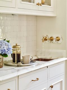 Butlers Pantry Sink and Faucet. Traditional Butlers Pantry Sink and Faucet. Traditional butler's pantry features glass front upper cabinets and white lower cabinets paired with white marble countertops and a white glazed tiled backsplash laid out in a brick pattern. Butler's pantry boasts a hammered copper sink placed under a wall mount gold spigot faucet. #butlerspantry #traditional #faucet #sink JackBilt Homes.