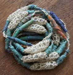 A necklace of crocheted hemp pods filled with crystals and wraps of sari silk around crocheted hemp chain.