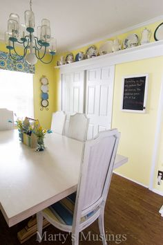Pale yellow and white dining room with touches of blue.