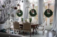 Christmas wreath accents on French doors and lovely branch decorations make for an elegant dining room.
