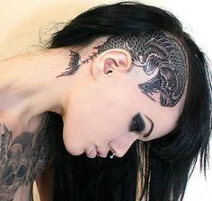 Septum, piercing de nariz y tatuaje en la cabeza.