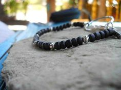 Pretty handmade black coconut shell and silver metal bracelet strung with super-strong black cotton cord. With large silver metal ring and lobster clasp. With black Japanese glass beads clasp detail. Simple and elegant on its own or with many others :) by FeekoByDesign, $6.00