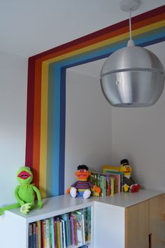Retro rainbow stripe painted up the wall, along the ceiling and down to suspended cloud shelf on the other side.